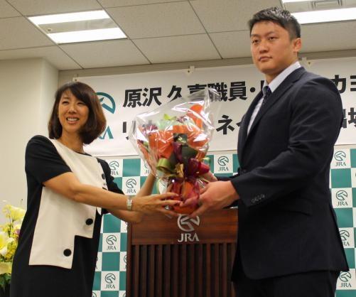 監事を務める小谷さんから花束を贈られる原沢(右)